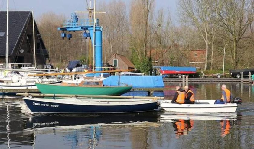 Werkbootje (wit) van watersportvereniging de Bommeer.