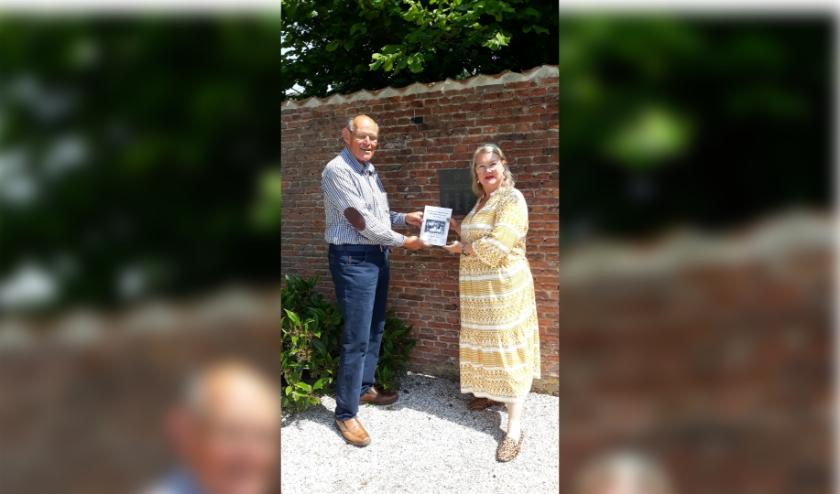De schrijver overhandigt het boek aan Daniëlle Stolk bij de plaquette van de 51 kinderen die op het Hof verbleven. De familie Stolk zijn de huidige bewoners van het Hof. (Foto: Privé)