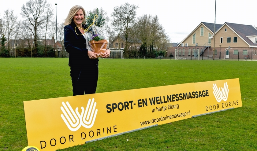 Dorine Verheul van 'Door Dorine Sport- en wellnessmassage' poseert met haar nieuwe reclamebord op sportpark De Heughte.