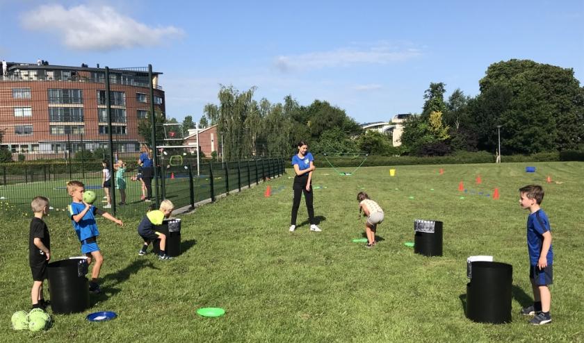 De Sportkaravaan vermaakt kinderen van groep 3 en 4 met sport en spel, hier bij het onderdeel Toren mikken (Kanjam). (foto: Marco Jansen)