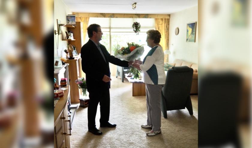 Voorzitter overhandigt bloemen aan Janny de Roode.