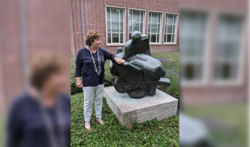Marita Damen voor het Kalsbeek College bij het kunstwerk 'Man met kruiwagen'. Tot 2003 zat hier de technische school (LTS).