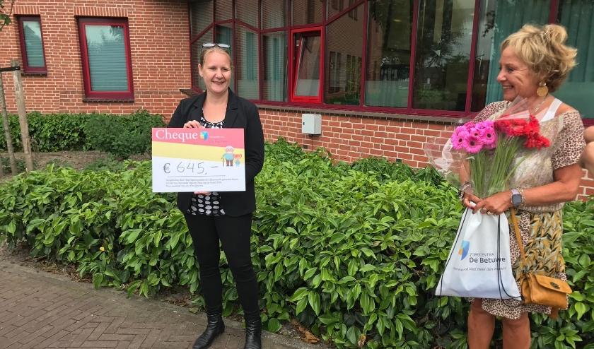 Medewerkers van Zorgcentra De Betuwe nemen cheque in ontvangst.