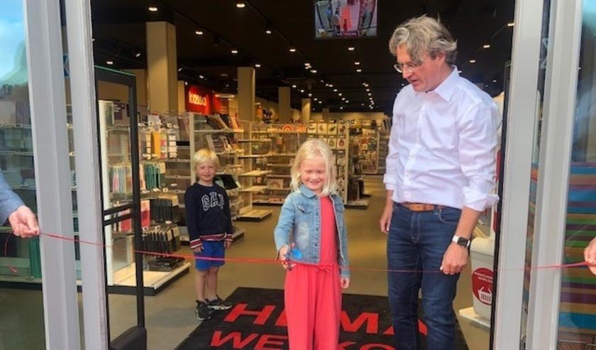 Dochter Quirine knipt onder toeziend oog van haar broertje en vader het lint door om de verhuisde Hema winkel officieel te openen