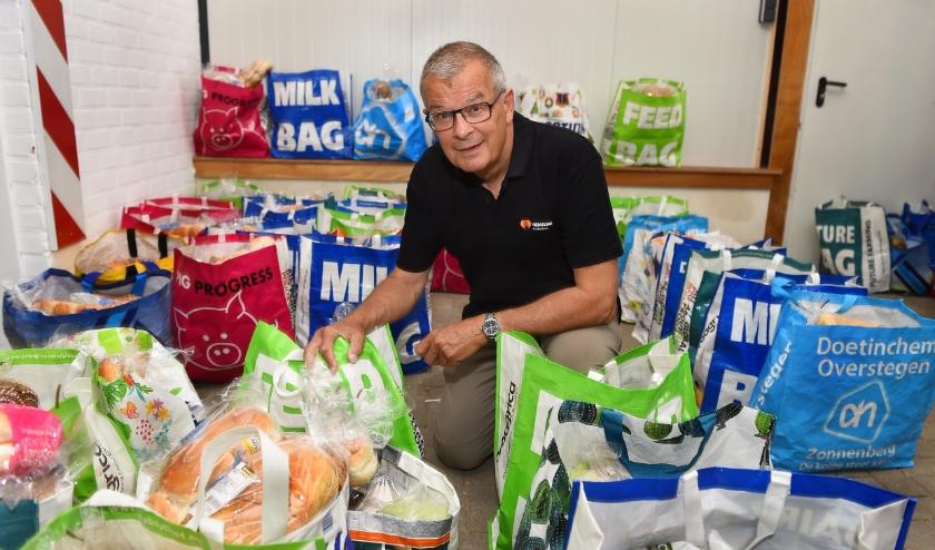Peter Bob Peerenboom, voorzitter van voedselbank Doetinchem, in het midden van de boodschappenpakketten. (foto Roel Kleinpenning)