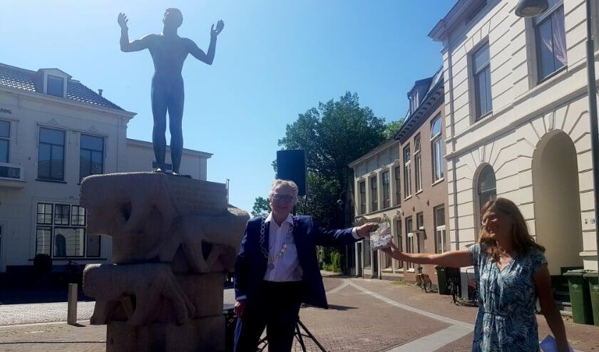 Lysbeth Beels overhandigde het eerste exemplaar van de wandelgids aan de burgemeester op het 5 Meiplein.(foto: Kees Stap)