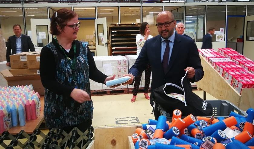 Burgemeester Marcouch helpt Olga van Scalabor met het inpakken van de pakketten.
