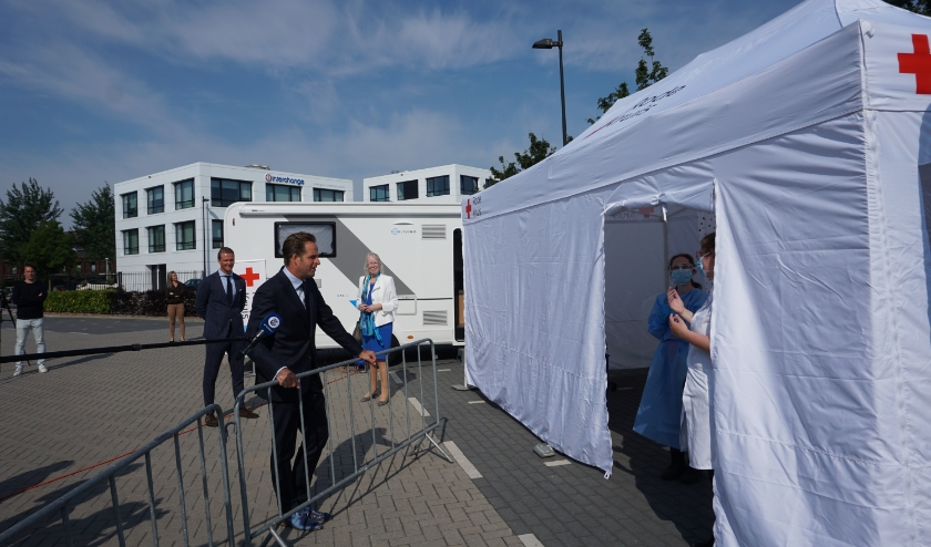 """De minister neemt de tijd voor een praatje met de medewerksters van de fietstent. """"Ik vond het wel spannend hoor"""", bekent Aranka (met het blauwe schort) achteraf (foto: Annemarie de Vries)."""
