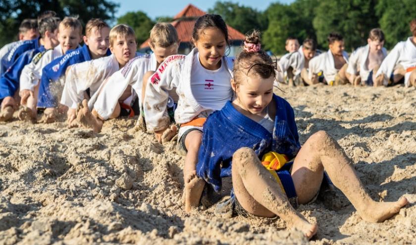 judoka's ploeteren door het zand op Het Rutbeek
