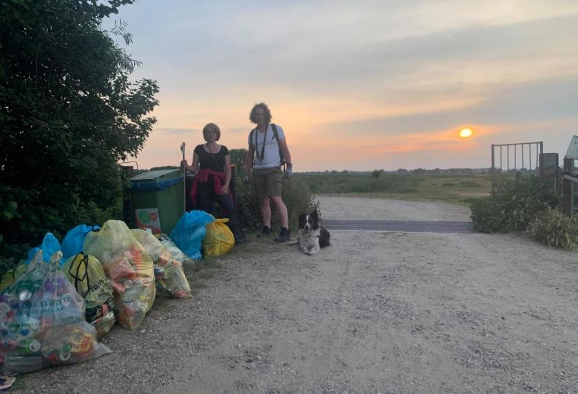 Terwijl de zon ondergaat poseren Marika Biacsics en Alexander te Witt bij de opbrengst van een middagje afvalruimen.