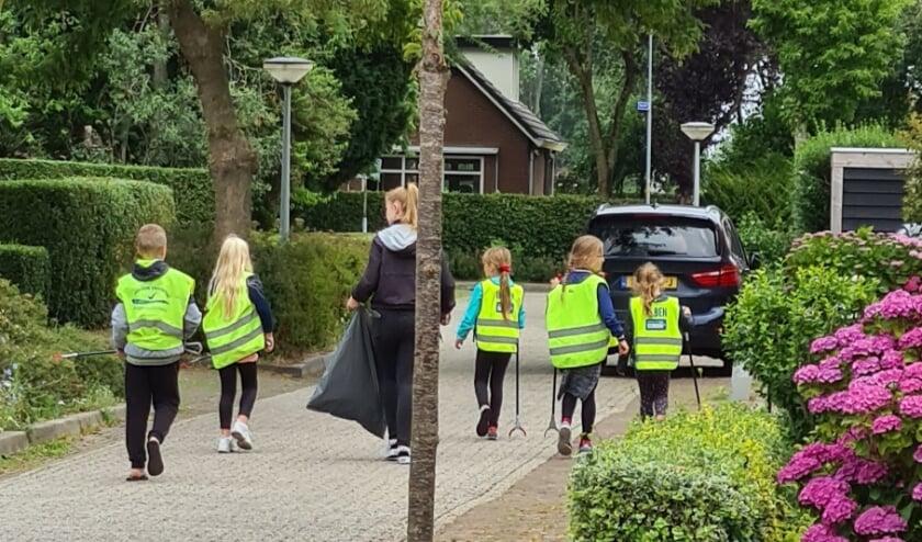 Kinderen van Basisschool De Hoge Hof ruimen afval op.