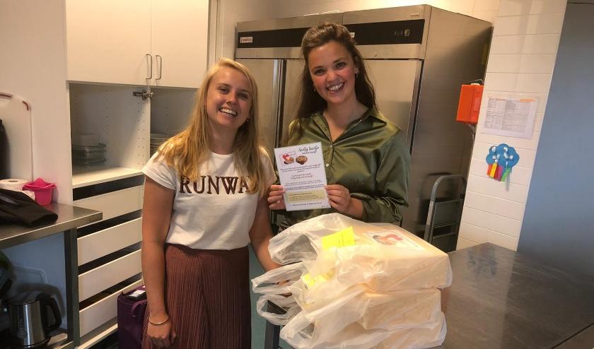 Lena en Carlijn (die samen in een studentenhuis wonen) met de hartige taartjes met een kaartje in het Doe mee Huis van M-Pact.