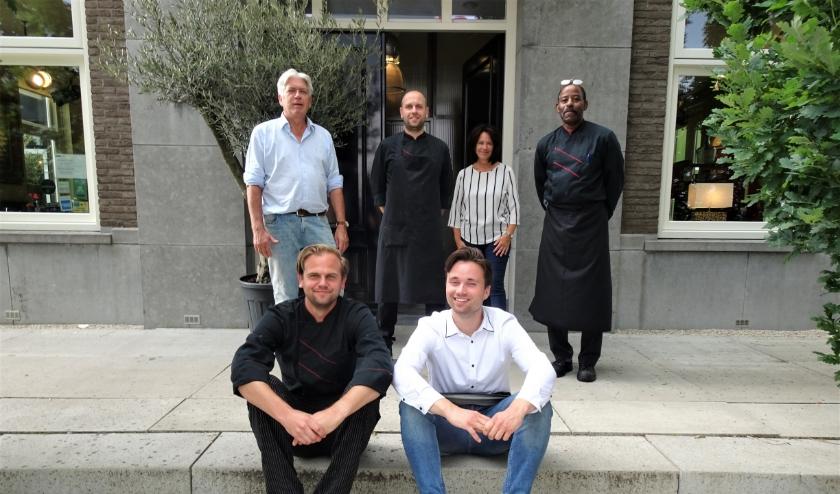 Aldert Bergwerff (linksboven)  en zijn vrouw voor het restaurant en te midden van het vriendelijke personeel. Tekst & foto: Joop van der Hor