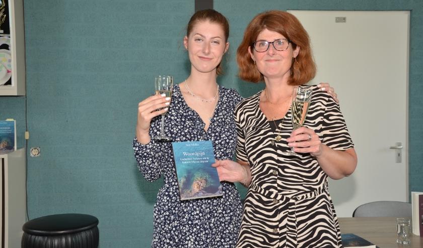 Sam Mollee en moeder Marie-José Spierings poseren met de gedichtenbundel 'Woordpijn' die onlangs werd gepresenteerd.