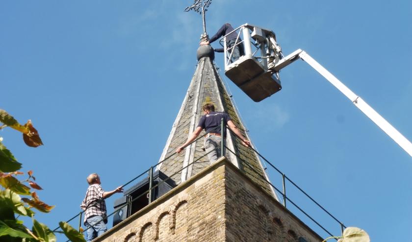 Piet Hogendoorn en aannemer Jan de Hoop kijken vanaf de torenomloop toe hoe metaalbewerker Arjan Hogendoorn de haan inspecteert. (Foto: Janneke Severs-Hilgeman)