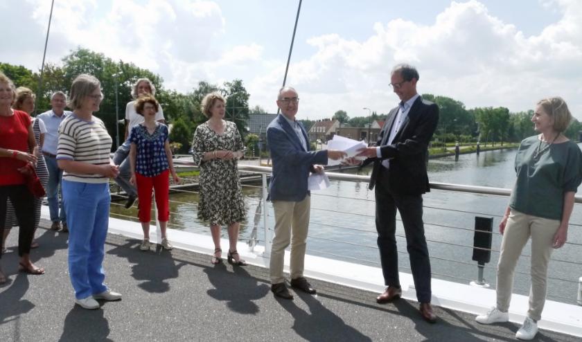 Namens bewoners uit de Bomenbuurt overhandigt Guy Alaerts (l) kopieën van de vele zienswijzen aan Menno van Enk (CDA).