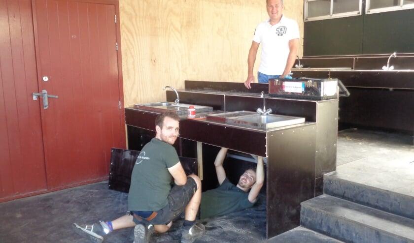 Patrick Berk (l) en Mats de Waal leggen de laatste hand aan de afwasplekken. Hugo Oudejans (r) is vol lof over de inspanningen van zijn medewerkers. Foto: Roy Visscher