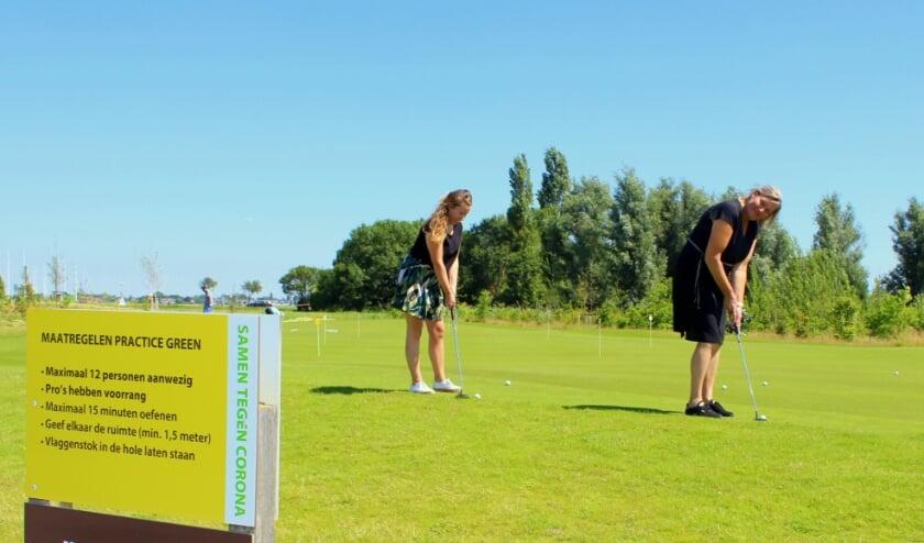 Carla Prins-Laban (re) en Amy Stolwijk laten zien hoe je coronaproof kunt golfen. Door de coronacrisis hebben veel mensen de golfsport ontdekt als veilige buitenactiviteit. FOTO: Morvenna Goudkade