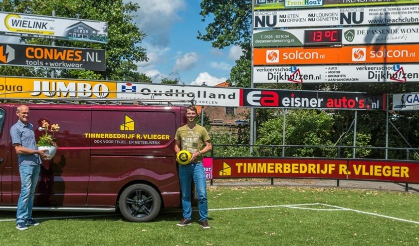 Rennie Vlieger (l) en Sjoerd Kwakkel bij het nieuwe reclamebord van Timmerbedrijf R. Vlieger op sportpak De Heughte.