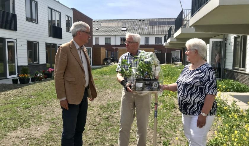Peter Hoogvliet, directeur MeerWonen, overhandigt twee vlinderstruiken aan de heer en mevrouw Verheij, nieuwe bewoners van het appartementencomplex