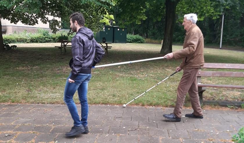 Een zorgvrijwilliger is onlangs  op pad geweest met een zorgvrager die zeer slechtziend is. Op deze manier kan 1.5 meter afstand worden gehouden. (Foto: Evenmens)