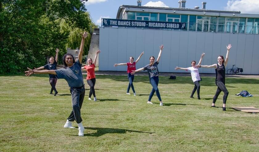 Ricardo Sibelo danst met zijn leerlingen op het grasveld. Foto: Gerard van Warmerdam