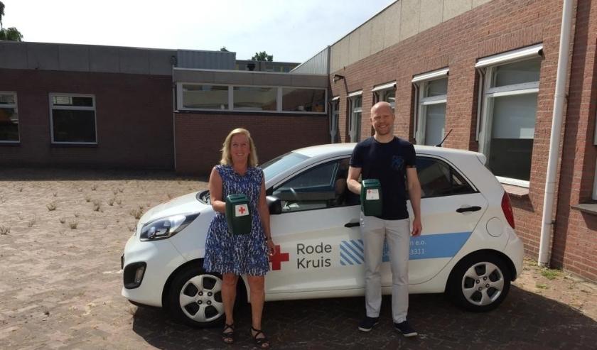 Anja van de Sande en Robin Pasman met in hun hand de bekende collectebus die nu plaats gaat maken voor een digitale variant.