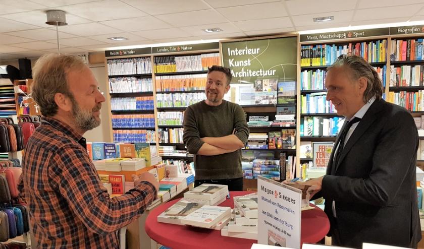Schrijver Marcel van Roosmalen (rechts) en Fotograaf des Vaderlands, Jan Dirk van den Burg in een geanimeerd gesprek met Ton Schulten.