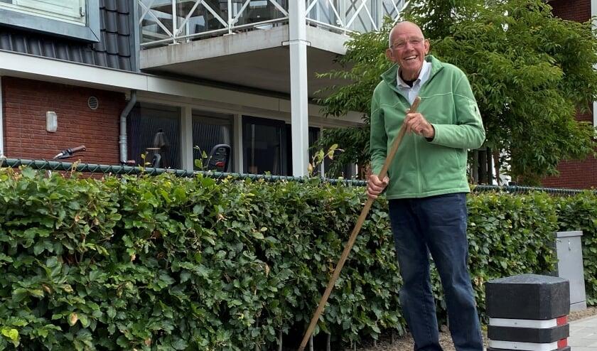 Klaas Ruting met schoffel en emmer in de aanslag aan zijn klusje buiten in de 'tuin'
