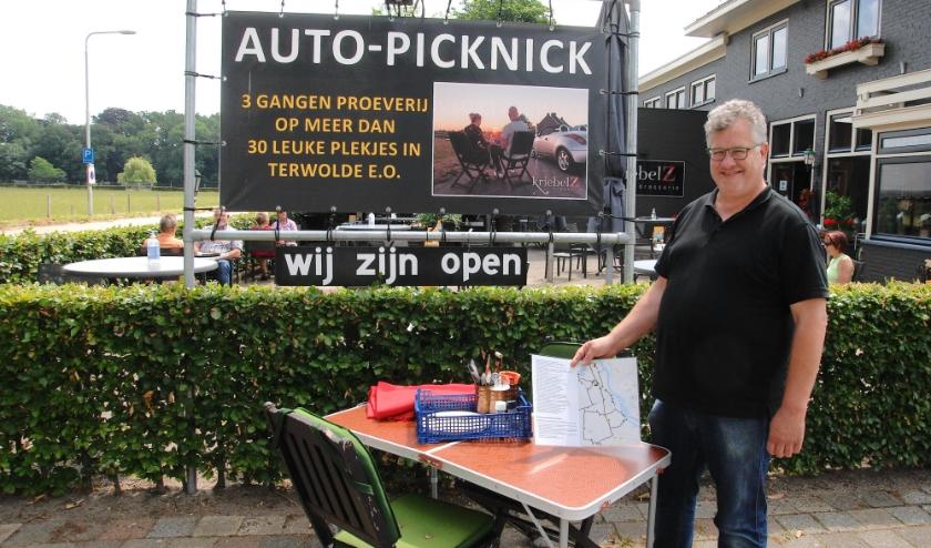 """René Zeisseink bij de tafel waar bestellingen voor de auto picknick kunnen worden opgehaald. ,,Gasten kunnen het eten meenemen naar een van de 34 mooie plekjes in en om Terwolde."""" (foto Gert Perdon)"""