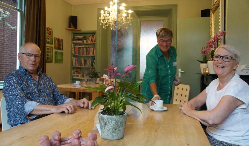 Vrijwilliger Annie van Vliet schenkt alweer koffie voor de gasten Sjaak Gresnigt en Corrie Gille.