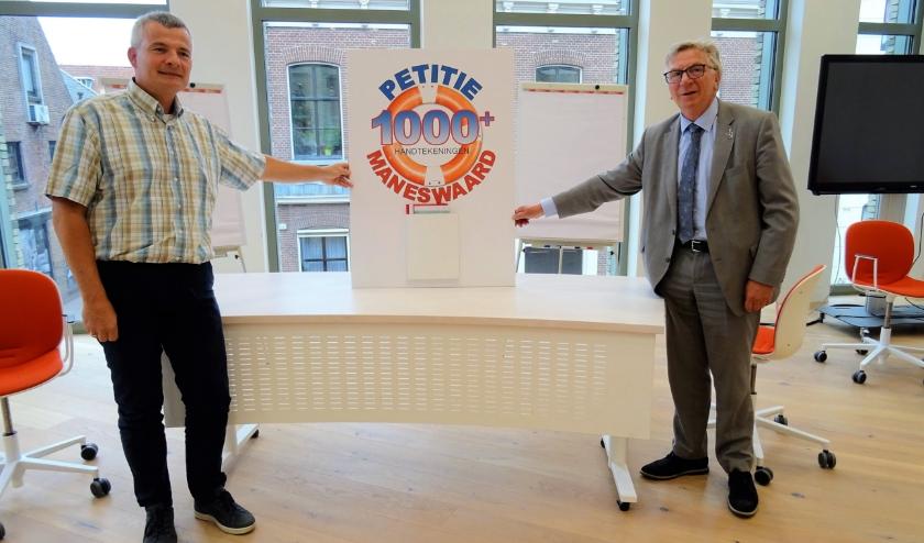 Frank Dankbaar (links) overhandigt de petitie, die afsluiting van Maneswaard moet voorkomen, aan burgemeester Geert van Rumund.