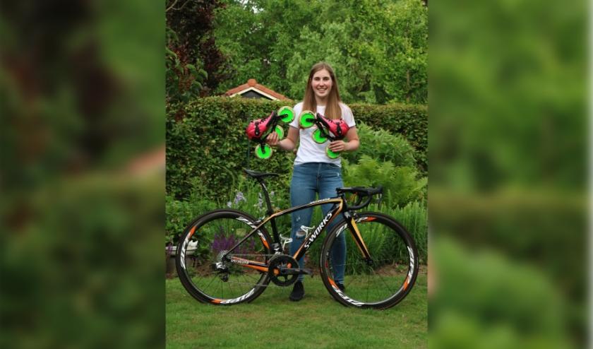 Lotte vrolijk lachend met haar twee grote liefdes op sportgebied: de racefiets en haar skeelers. (foto: Marcel Reintjes)