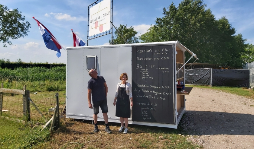 Bart en Antoinette Leenders van boerderijwinkel Natuurlijk Kersvers bij hun coronaproof drive-in kraampje vol kersen, aardbeien, wafels en ijs.