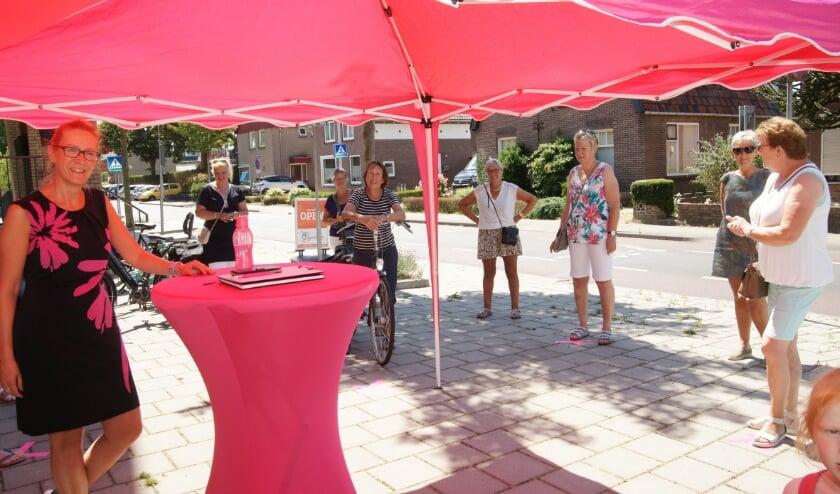 Janiek Kroon (links) verwelkomt buiten de belangstellenden tijdens de zogeheten 'walk-by' bij haar sportinstituut aan de Kerkstraat in Westervoort.