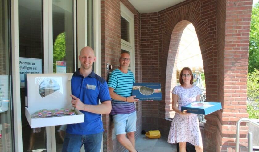 """Medewerker Edwin van De Jong leverde de dozen haring af bij welzijnsmedewerkers Michel en Liesbeth: """"Ze hebben allemaal wel een extraatje verdiend na de intensieve maanden."""" (Foto: Lysette Verwegen)"""