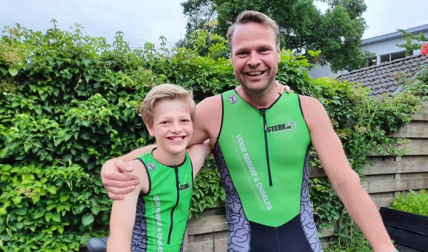 Zoon Ties en vader Jasper in hun speciale pakken waarin ze hun triathlon willen gaan volbrengen