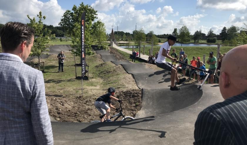 Wethouder Jeroen de Jong (links) ziet één van de kinderen een spectaculaire sprong maken op de nieuwe pumptrackbaan. (foto: Marco Jansen)