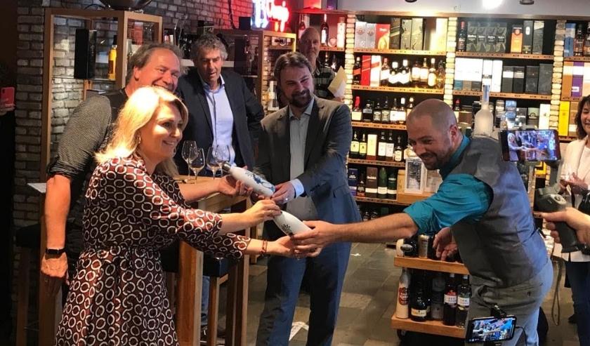 Lara Melkert en Jacques Tange reiken twee Schiedam Blue Bottles uit aan wethouders Jeroen Ooijevaar en Duncan Ruseler. Ben de Koning van de Frankelandgroep en Rob van der Drift van NME De Harreweg kijken geamuseerd toe.