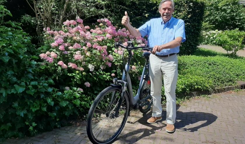 Oud-huisarts Aad Schreuders bij de e-bike die hij met de afscheidsbijdragen van patiënten heeft aangeschaft.