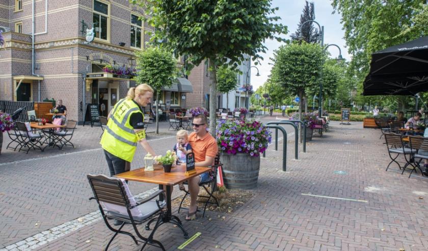 Het personeel van De Postkamer in Heerde heeft hesjes aan en een aanvoerdersband om met 'houd afstand 1,5 meter' er op. (Foto: Dennis Dekker)