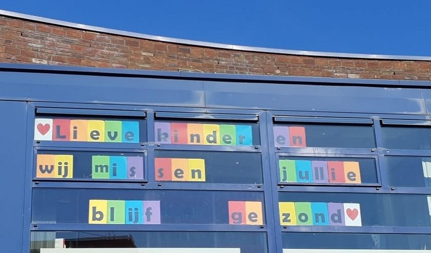 De meesters en juffen van De Regenboog met een boodschap voor hun leerlingen.