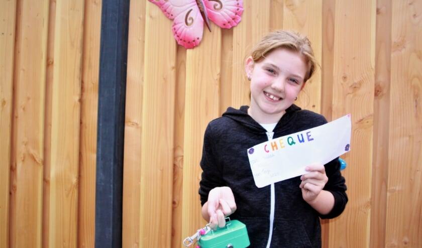 Een trotse Faye Harteman met haar cheque, een zelfgemaakte schelpenketting en haar geldkistje. (foto: Arno voor de Poorte)