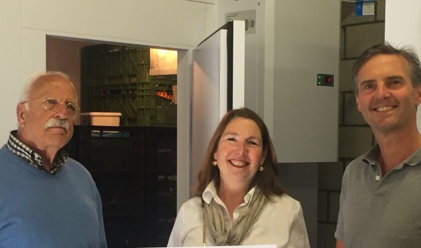 Voorzitter van de voedselbank, Jolanda van Hulst, staat met de heren Lindenbergh (l) en van Driel (r) van de Lionsclub De Bilt Bilthoven voor de koelinstallatie.