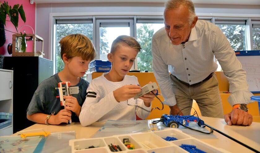 Pedro Jooren kijkt toe als Tjeerd en Dylan tijdens de Techniekles op de Heeswijkschool een elektrische auto bouwen. (Foto: Paul van den Dungen)