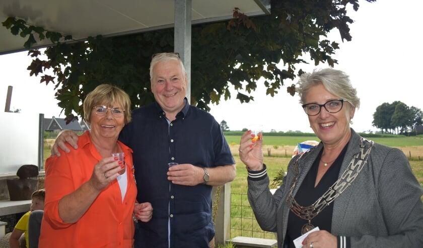 Herma en Henk Mennegat brengen samen met burgemeester Doret Tigchelaar een toost uit.