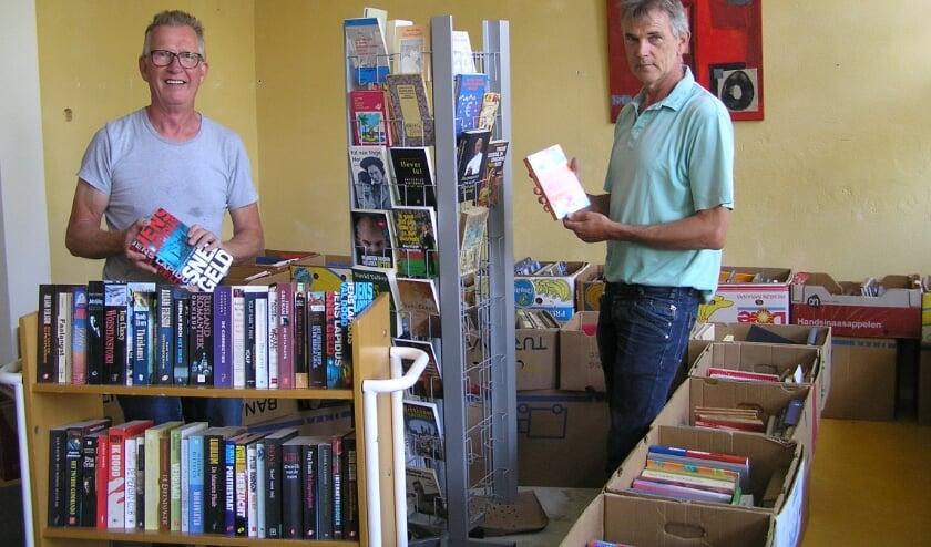 Vrijwilligers Ton Meijer en Wim Jansen zijn razend druk met de inrichting.