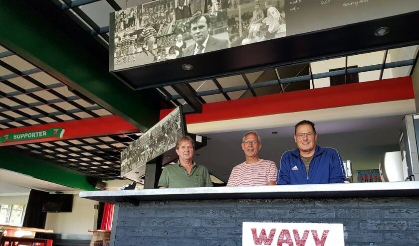 Geurt Hellegering, Ton Bongers en Fred Albers (vlnr) staan vol trots achter de volledig gerenoveerde bar, opgesierd met een fraaie fotocollage.