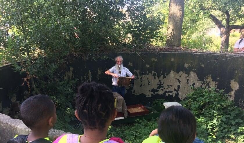 Chris van Iersel toont de kinderen van de Zomerschool 2019 een bijenraat.
