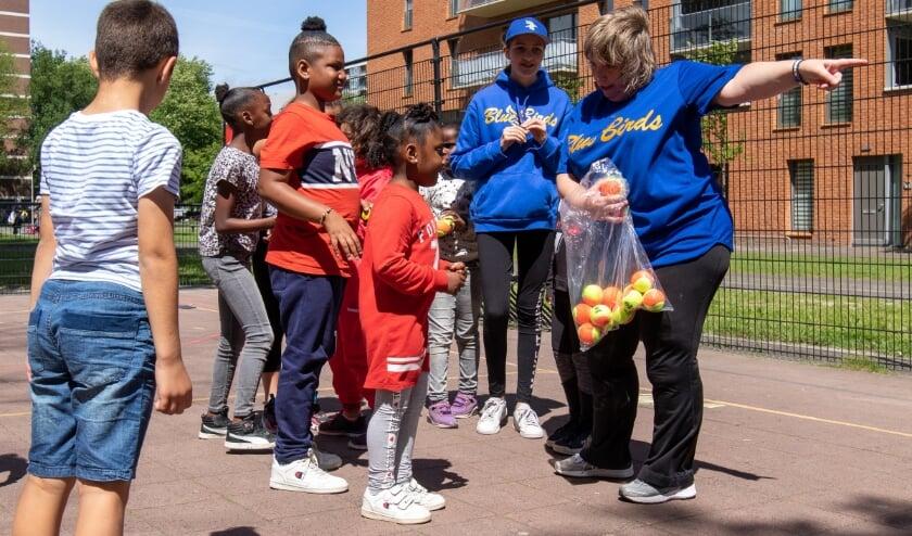 Krista van Meijgaarden van de Blue Birds (rechts op de foto)legt de jeugd van de Poptahof de basics van baseball 5 uit.